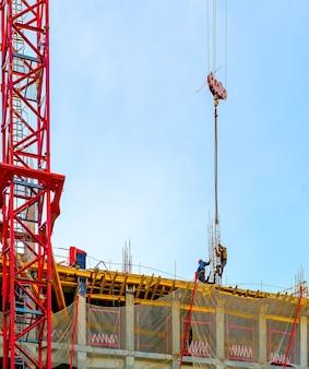 建物の建設におけるクレーンと労働者