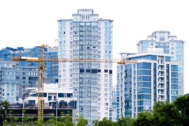 Crane on a construction site of building of modern residential district high apartment buildings or skyscrapers in a new elite complex.