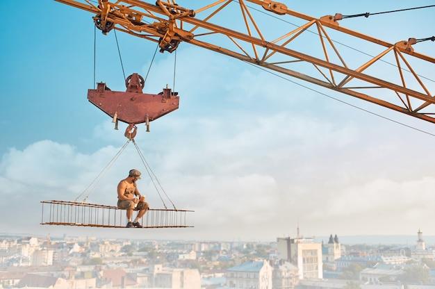 Кран держит железную конструкцию, где сидит строитель с голым торсом, ест и пьет молоко. экстремальное здание на высоте. городской пейзаж на фоне.