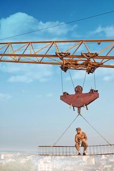Кран держит железную конструкцию, где сидит строитель