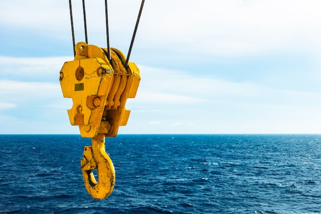 Crane hook in the sea with sky and clouds background on offshore platform