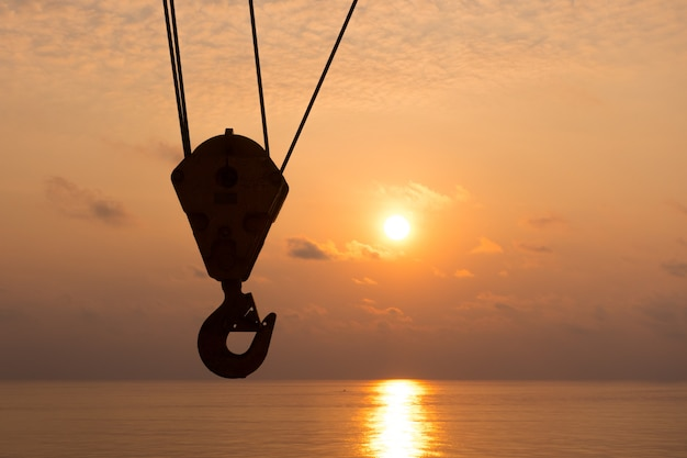 Crane hook silhouette in sunset time with sea background in offshore oil and gas platform