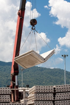 Кран поднимает бетонные плиты на строительной площадке
