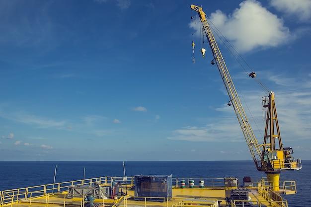 근해 산업 석유 및 가스 바다와 푸른 하늘을 들어 올리는 크레인.