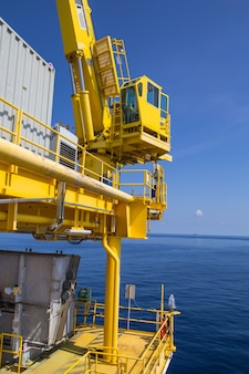 Crane lifting offshore industrial oil and gas sea and blue sky.