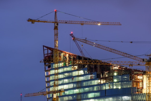 밤에 공사중 건물 위에 크레인.