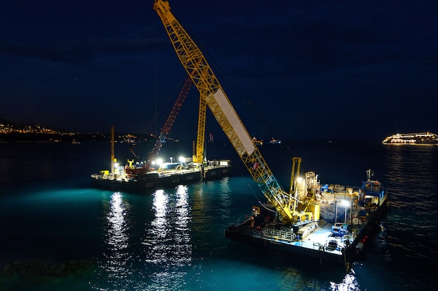 Crane vessels on water at night