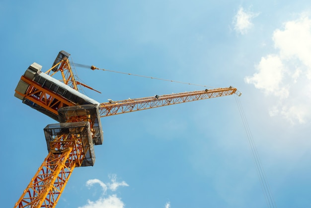 Crane workers at the construction site and blue sky
