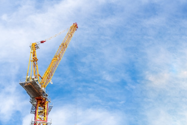 Crane working in construction site with cloud and blue sky in background with copy space.