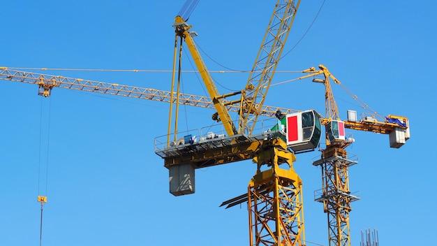Кран, работающий на строительной площадке и тяжелый стальной материал, желтый цвет и голубое небо