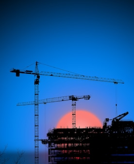夜明けのクレーンと建物のシルエット