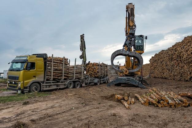 Краны на территории склада бревна выгружаются из грузовика.