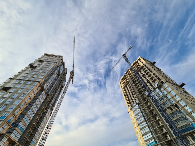 Cranes standing near multistorey buildings under construction against background of blue sky bottom ...