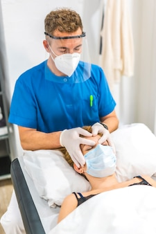 Cranial osteopathy, cranial massage by a physical therapist with protective measures for a patient on the stretcher. covid-19 pandemic. osteopathy, therapeutic chiromassage
