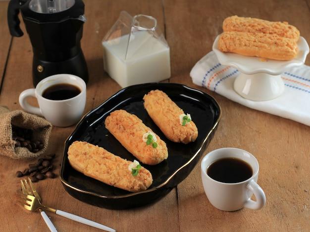 Craquelin eclair, 상단에 호랑이 모티브가 있는 맛있는 프랑스 슈 페이스트리 디저트(craquelin), 커피와 함께 제공됩니다. 베이커리 티 타임 개념