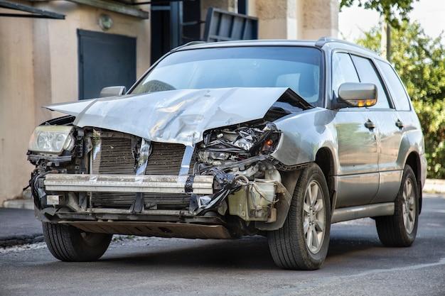 자동차 사고로 추락 한 자동차. 치명적인 재난 후 차량 고장. 도로 충돌 피해. 회색 자동차는 사고로 손상됩니다. 충돌 후 자동차 손상.