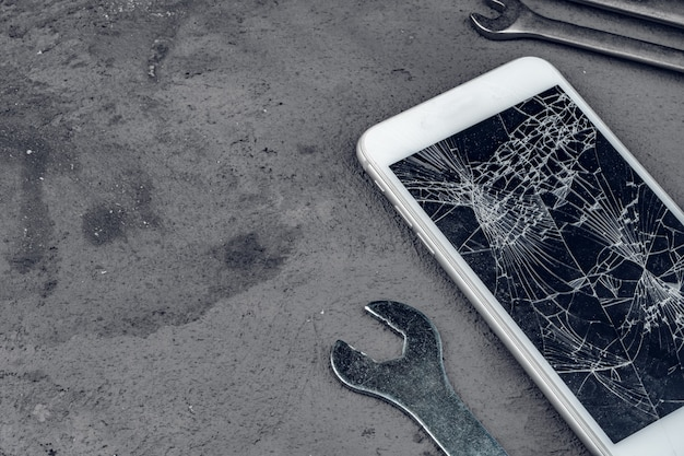 Crashed smartphone with repairing tools on grey background