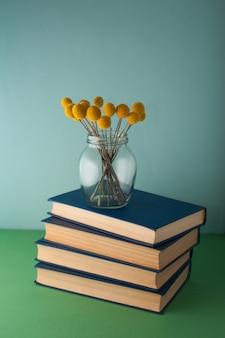 Стопка книг и цветов craspedia