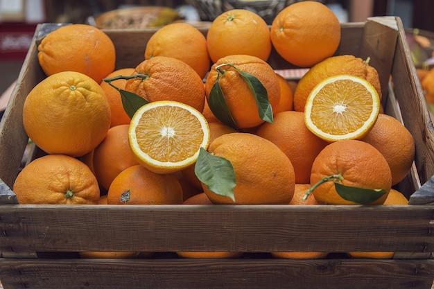新鮮なオレンジ色の果物でいっぱいの木枠