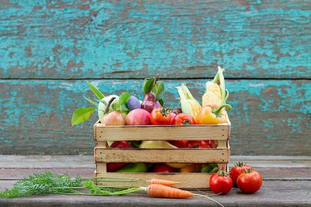 熟した農場の果物と野菜の素朴な剥離ペイントの木製の背景の木枠。