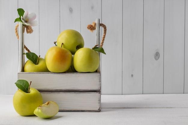 Ящик с вкусными зелеными яблоками на белом деревянном столе, пустое пространство. сочные органические фрукты