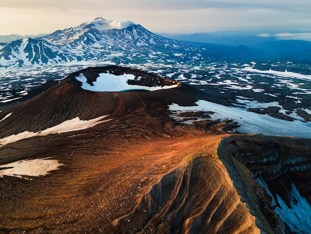 Crater of gorely volcano and mutnovsky volcano in the background. kamchatka peninsula, russia. beautiful landscape at sunrise.