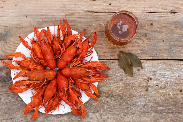 Crawfish and beer on the old wooden background. top view.