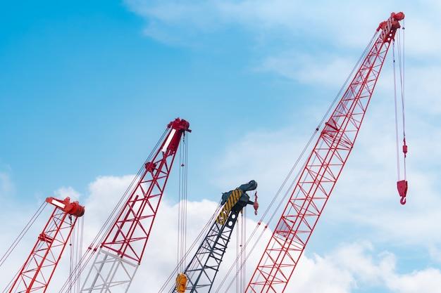 푸른 하늘과 흰 구름에 대 한 크롤러 크레인입니다. 부동산 산업입니다. 레드 크롤러 크레인은 건설 현장에서 릴 리프트 장비를 사용합니다. 크레인 임대. 건설 사업을 위한 크레인 대리점.