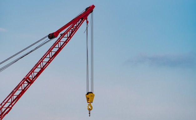 Crawler crane against blue sky and white clouds real estate industry red crawler crane
