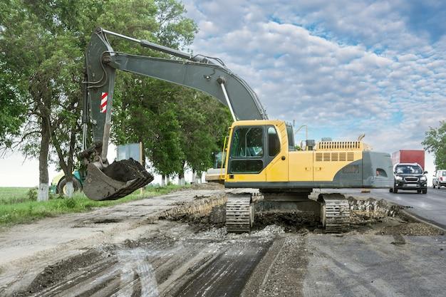Гусеничный экскаватор ремонтирует дорогу