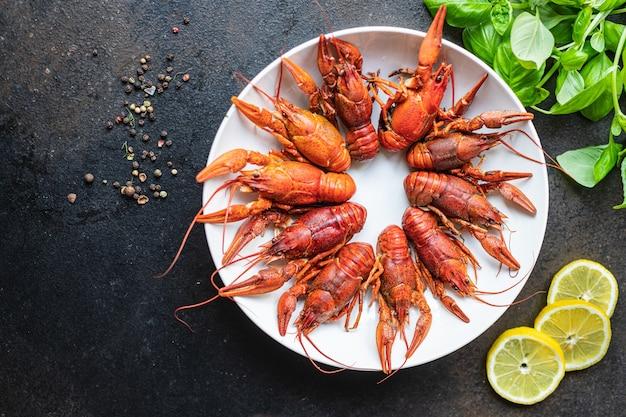 ザリガニの新鮮な茹でた甲殻類は、テーブルのコピースペースの食べ物の背景に食事の軽食を食べる準備ができています
