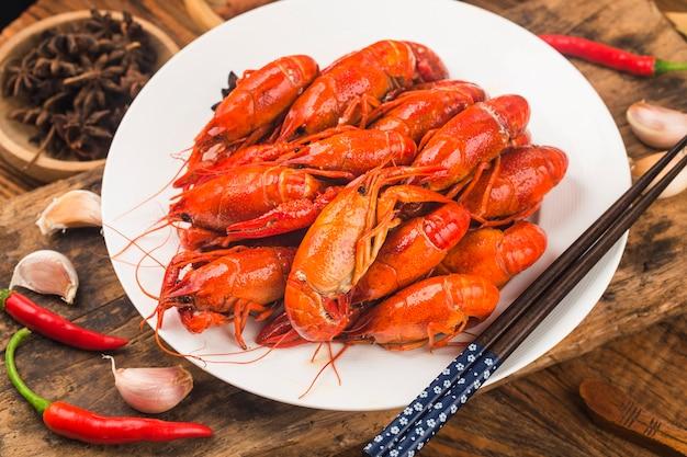ザリガニ。素朴なスタイルのテーブルの上の赤茹でたクロウフィッシュ、ロブスターのクローズアップ。