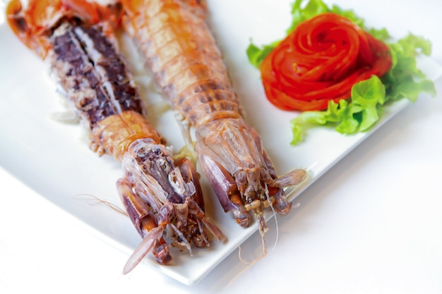 Crayfish on white dish served with dipping sauce.