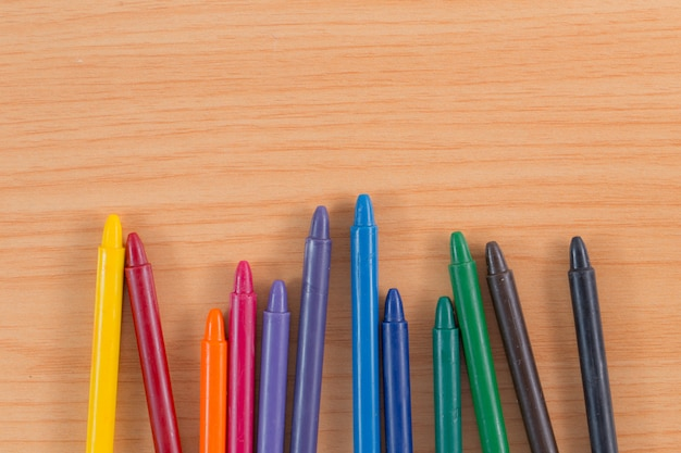 Crayon colors on wood background with copy space