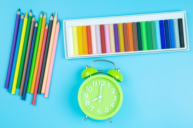 Crayon green clock on blue background pastel style
