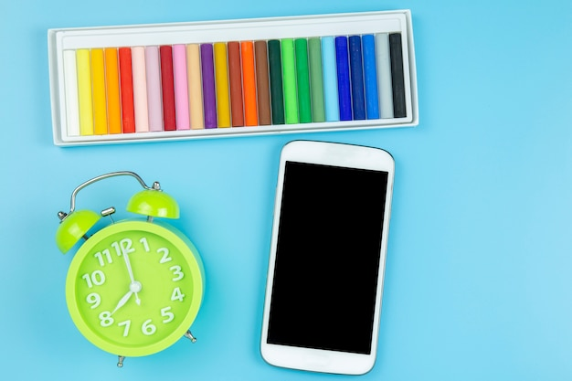 Crayon green clock and mobile on blue background pastel style