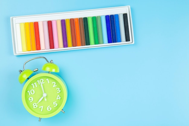 Crayon and green clock morning on blue background pastel style with copyspace.