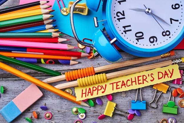 Мелки, будильник и открытка. поздравление с национальным днем учителя.