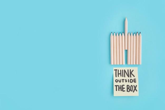 Мелки цветной карандаш и думать вне коробки текст на заметку на синем фоне