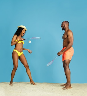 Craziest fun. happy young african-american couple playing badminton on blue studio background. concept of human emotions, facial expression, summer holidays or weekend. chill, summertime, sea, ocean.