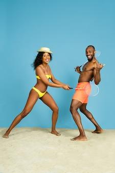 クレイジーな楽しみ。青い空間でバドミントンをしている幸せな若いアフリカ系アメリカ人のカップル