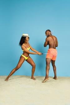 미친 재미. 행복 한 젊은 아프리카 계 미국인 커플 블루 스튜디오 배경에 배드민턴. 인간의 감정, 표정, 여름 방학 또는 주말의 개념. 진정, 여름, 바다, 바다.