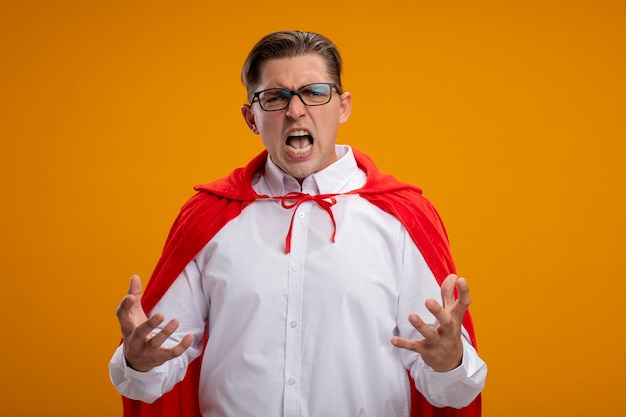Crazu mad angry super hero businessman in red cape and glasses shouting with raised hands standing over orange background