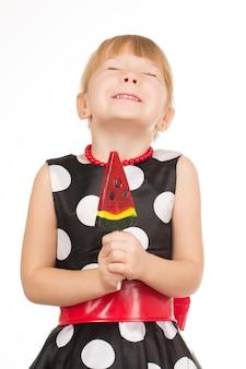 お菓子に夢中。ロリポップを持って目を閉じて興奮して笑っているドレスを着ている女の子の縦の肖像画
