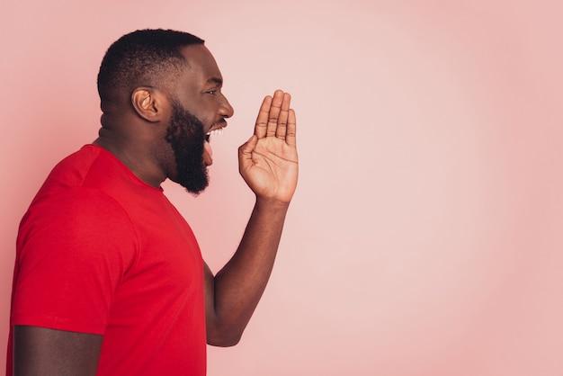 미친 아프리카 남자는 분홍색 배경 위에 고립된 손을 잡고 소리를 지른다