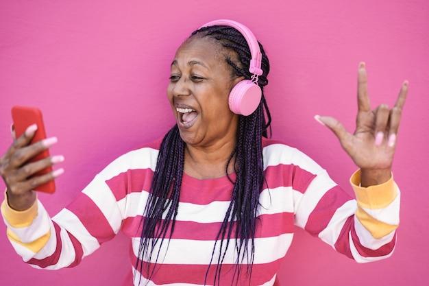 Сумасшедшая африканская старшая женщина слушает музыку в приложении для мобильного телефона - сосредоточьтесь на лице