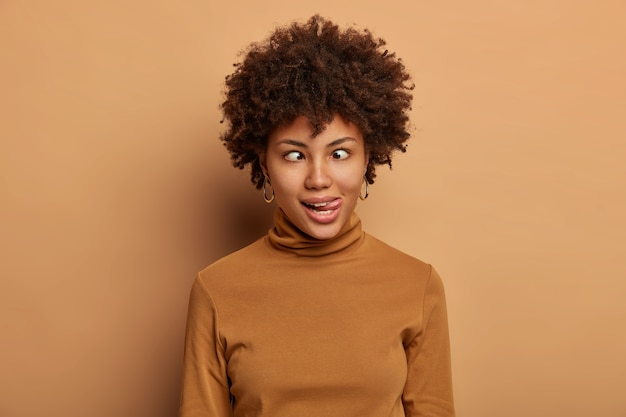 Crazy afro american woman makes funny face, sticks out tongue and crosses eyes, fools around, wears casual brown turtleneck