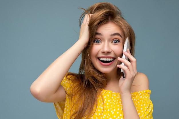 Сумасшедший изумлен удивлен молодая женщина в повседневной стильной одежде, стоящая изолированно на фоне с копией пространства, держащей и использующей мобильный телефон, глядя в камеру.