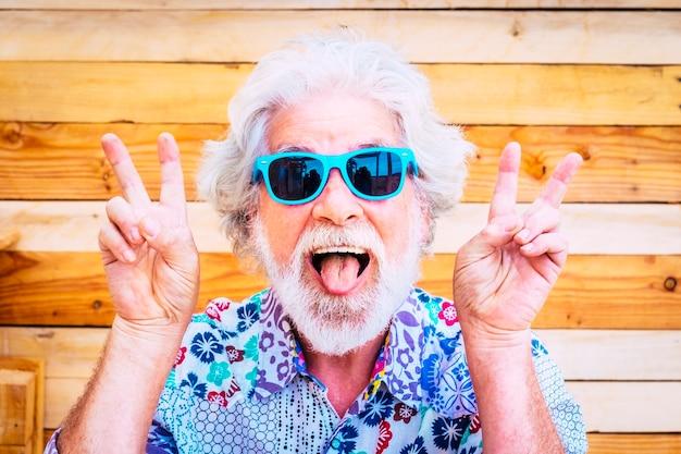 Сумасшедший и счастливый активный молодой старший мужчина делает забавное выражение руками победителя