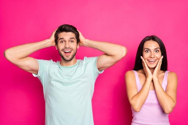 미친 검은 금요일! 놀라운 커플 남자와 낮은 쇼핑 가격을 찾고 여자의 사진은 생생한 핑크 색상 배경에 고립 된 캐주얼 세련된 옷을 입고